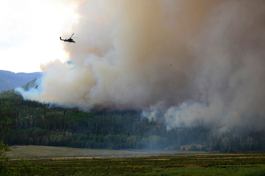 . A helicopter carries a bucket of water as the Papoose fire continues to burn near Creede. The three fires that make up the West Fork Complex fire now top out at more than 70 thousand acres. (Photo by AAron Ontiveroz/The Denver Post)