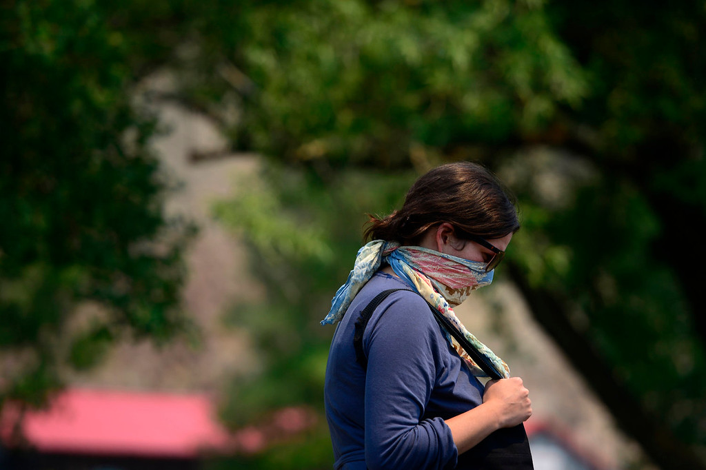 . A woman covers her face to help aid against the smoky haze near downtown. The West Forest Complex fire continues to burn as it feeds on vast amounts of beetle kill in the surrounding forest. As a result, Creede, a town that relies on the summer months\' cash flow to get them through long winters is as empty in June as anyone in the area can remember. (Photo by AAron Ontiveroz/The Denver Post)