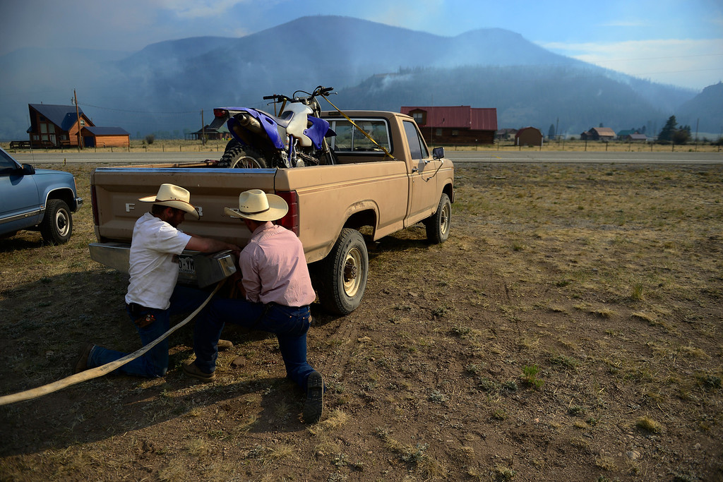 . Wranglers from left to right Dusty Weller and Chris (no last name) adjust a tow strap while fixing a fence as the air is filled with a smoky haze from the West Fork Fire burning near Creede. The West Fork Fire grew to more than 70,000 acres overnight. (Photo by AAron Ontiveroz/The Denver Post)