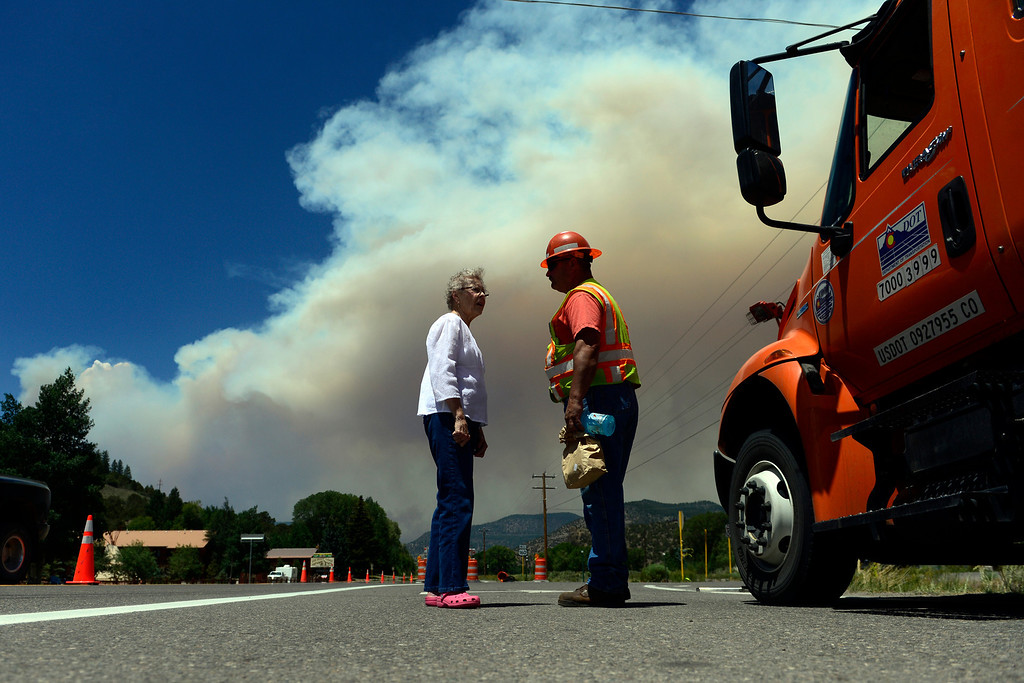. CDOT worker Brett Murrelle speaks with Le Shepherd at the Highway 160 roadblock as the West Fork Fire continues to burn near South Fork. The West Fork Fire grew to more than 70,000 acres overnight. (Photo by AAron Ontiveroz/The Denver Post)