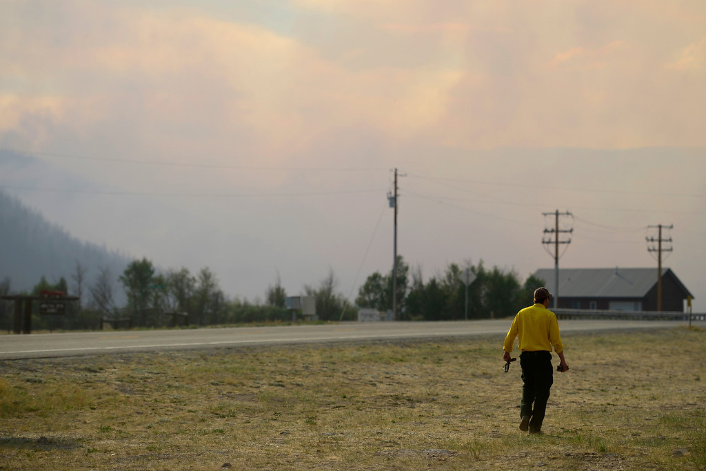 . EMT Chris Haefner, of Laramie, Wyoming, walks along the roadside in a smoky haze as the West Fork Fire continues to burn near Creede. The West Fork Fire grew to more than 70,000 acres overnight. (Photo by AAron Ontiveroz/The Denver Post)