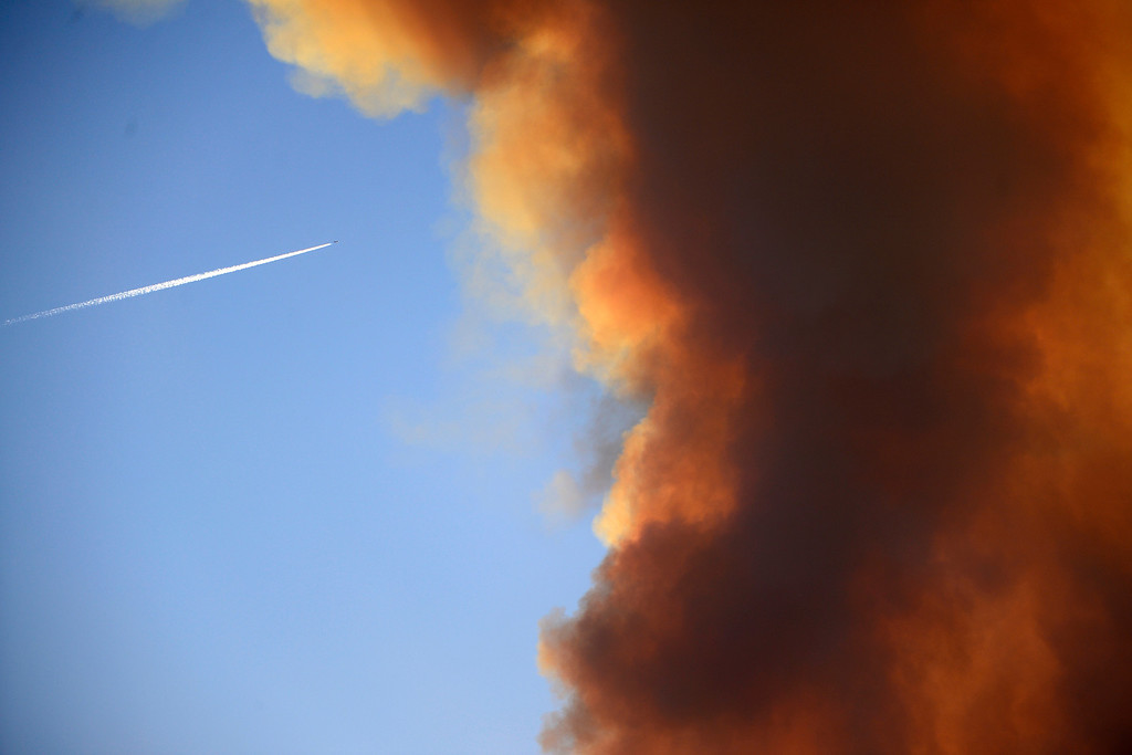 . CREEDE, CO - JUNE 25: A commercial plane flies overhead as the Papoose fire continues to burn at sunset near Creede. The three fires that make up the West Fork Complex fire now top out at more than 70 thousand acres. (Photo by AAron Ontiveroz/The Denver Post)