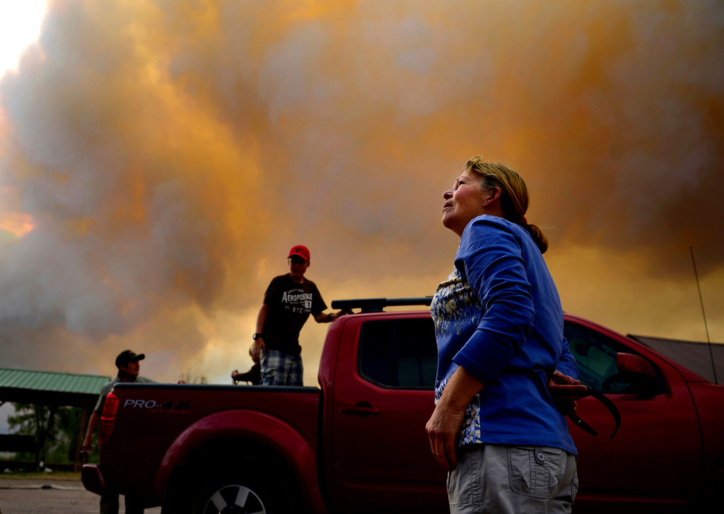 . Sheryl Forrester looks to the smoke-filled sky as the Papoose fire heats up near Creede, Colo., on June 24, 2013. The Papoose fire combined with two other fires to create the West Fork Complex fire, which burned more than 100,000 acres in southwest Colorado.
