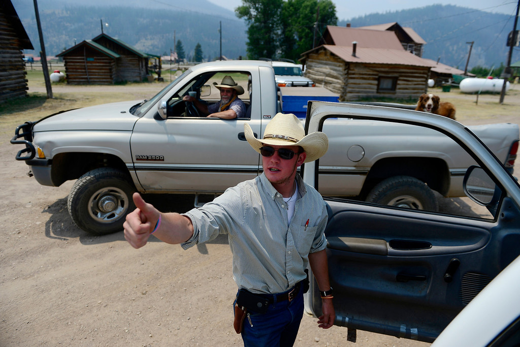 . Chris Cage gives the thumbs up to fellow wranglers while preparing to return more than 20 horses to their pasture across Highway 149 as the Papoose fire continues to burn near Creede. The three fires that make up the West Fork Complex fire now top out at more than 80 thousand acres. (Photo by AAron Ontiveroz/The Denver Post)