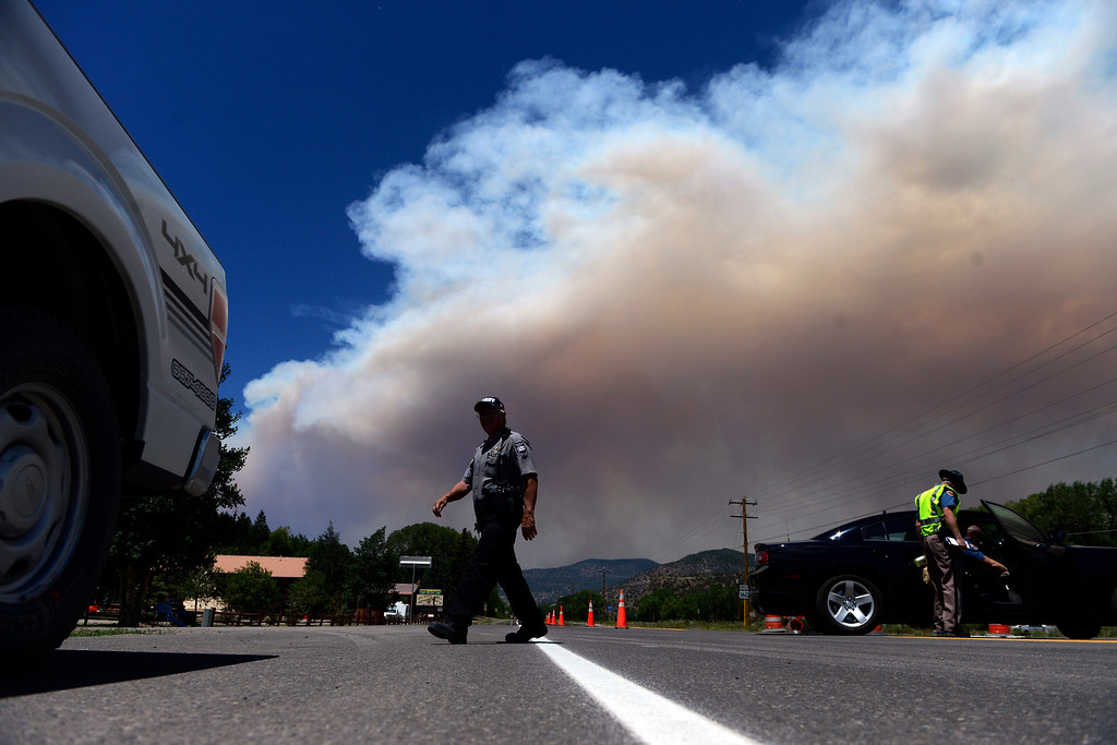 . A sheriff\'s deputy walks across the roadblock on Highway 160 as the West Fork Fire continues to burn near South Fork. The West Fork Fire grew to more than 70,000 acres overnight. (Photo by AAron Ontiveroz/The Denver Post)