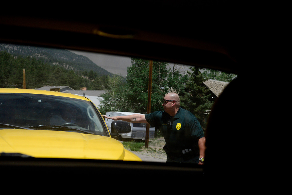 . Officer James Chavez of the South Fork Police touches hands with Ron Marx as he supports the homeowner after he and his wife left her home as the West Fork Fire continues to burn near South Fork. The West Fork Fire grew to more than 70,000 acres overnight. (Photo by AAron Ontiveroz/The Denver Post)