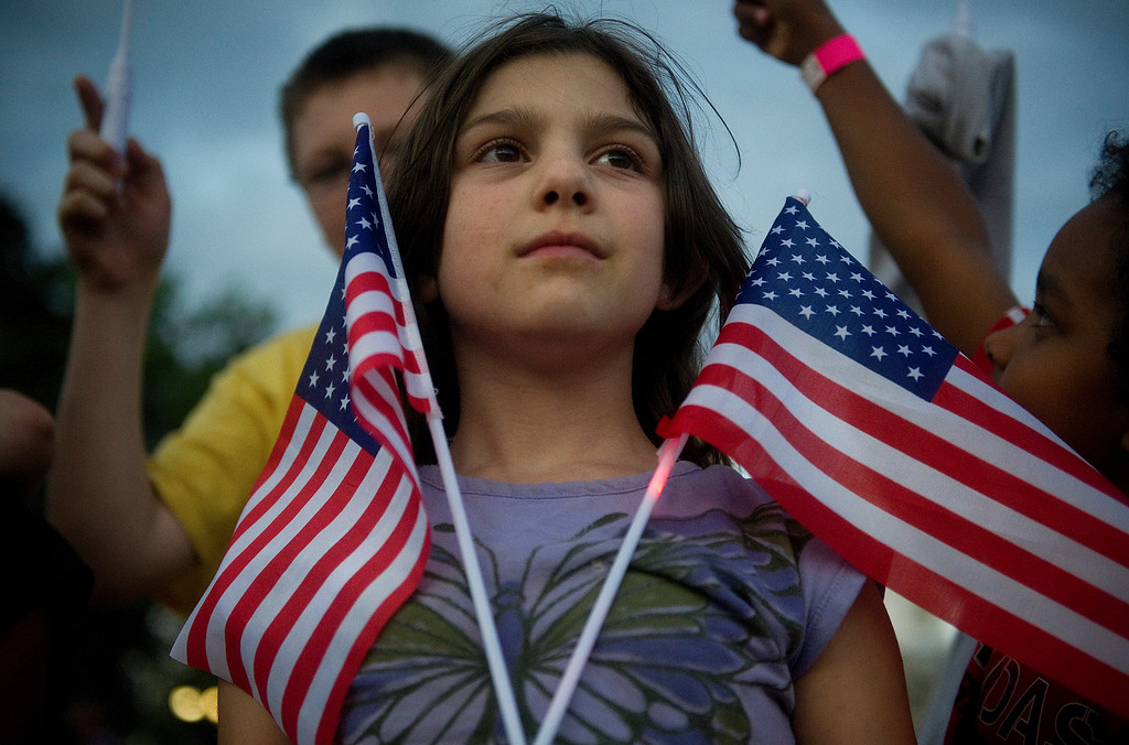 . DENVER - JUNE 28: Dravyn Welchman, 9, waves two American Flags in anticipation of the Colorado Symphony and fireworks at Civic Center Park on July 2, 2013. (Photo By Grant Hindsley / The Denver Post)