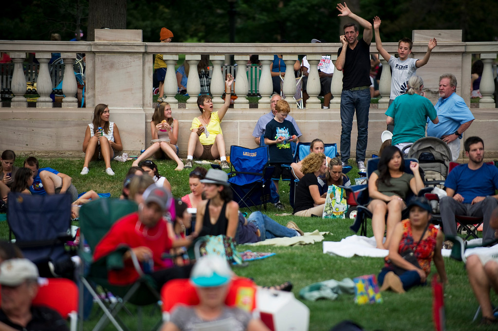 . DENVER - JULY 3: Families and friends wave down other spectators before the Colorado Symphony took the stage during the Indepenence Day celebration at Civic Center Park in Denver on July 3, 2013. (Photo By Grant Hindsley/The Denver Post)