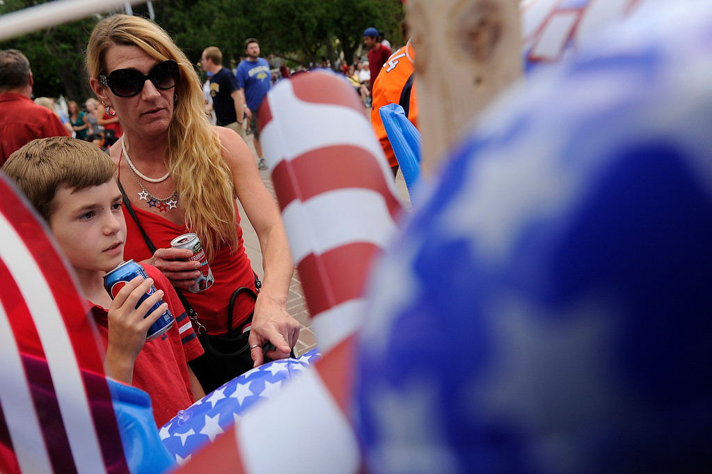 . DENVER, CO - JULY 3: Lisa Krecklow, right, and Garrett Krecklow, her son, look to buy souvenirs before the city of Denver\'s annual fireworks show off the City and County Building in Civic Center on July 3, 2013, in Denver, Colorado. (Photo by Daniel Petty/The Denver Post)