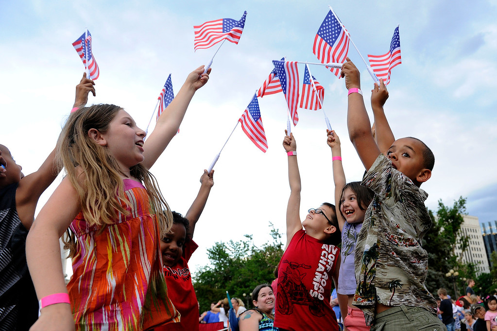 . DENVER, CO - JULY 3: Children play with American flags in Civic Center before the city of Denver\'s annual fireworks show off the City and County Building on July 3, 2013, in Denver, Colorado. (Photo by Daniel Petty/The Denver Post)