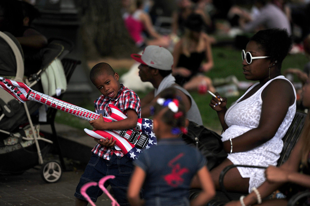 . DENVER, CO - JULY 3: A boy plays air guitar as spectators picnic before the city of Denver\'s annual fireworks show off the City and County Building in Civic Center on July 3, 2013, in Denver, Colorado. (Photo by Daniel Petty/The Denver Post)