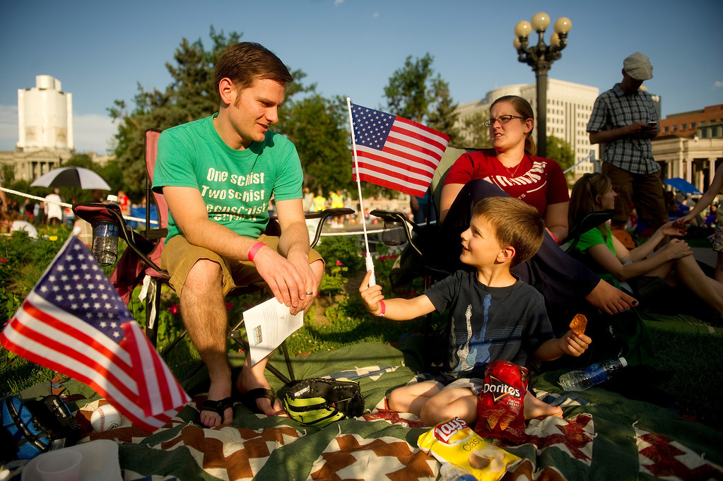 . DENVER - JULY 3: Joe Phillips, 5, shows his dad, Stephen, his flag while sitting with his mother, April and his younger brother, Stephen, not pictured, at Civic Center Park in Denver on July 3, 2013. The Colorado Symphony will play during the fireworks show. (Photo By Grant Hindsley/The Denver Post)
