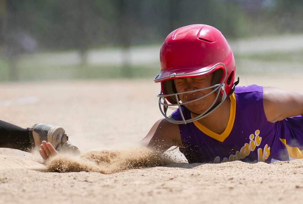 . AURORA, Co. - JULY 4: #6 of the Hawaii Pearls Ariana Badua slides back into first base after leading off during a pool play baseball game against the Oklahoma Firebirds at the Colorado Fireworks 2013 softball tournament on July 4, 2013 at Aurora Sports Park. The tournament brings hundreds of teams from across the nation to compete against one another and is a hot spot for college scouts. (Photo By Grant Hindsley/The Denver Post)