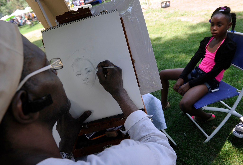 ". DENVER, CO - JULY13: Artist Robert Evans uses a pencil to make the perfect likeness of Jaelyn Odoms, 9. The 27th Annual Colorado Black Arts Festival takes place in City Park with this year\'s theme ""African American Style: an American Legacy. The festival continues through Sunday with dozens of artists, vendors, and performances taking place. (Photo By Kathryn Scott Osler/The Denver Post)"