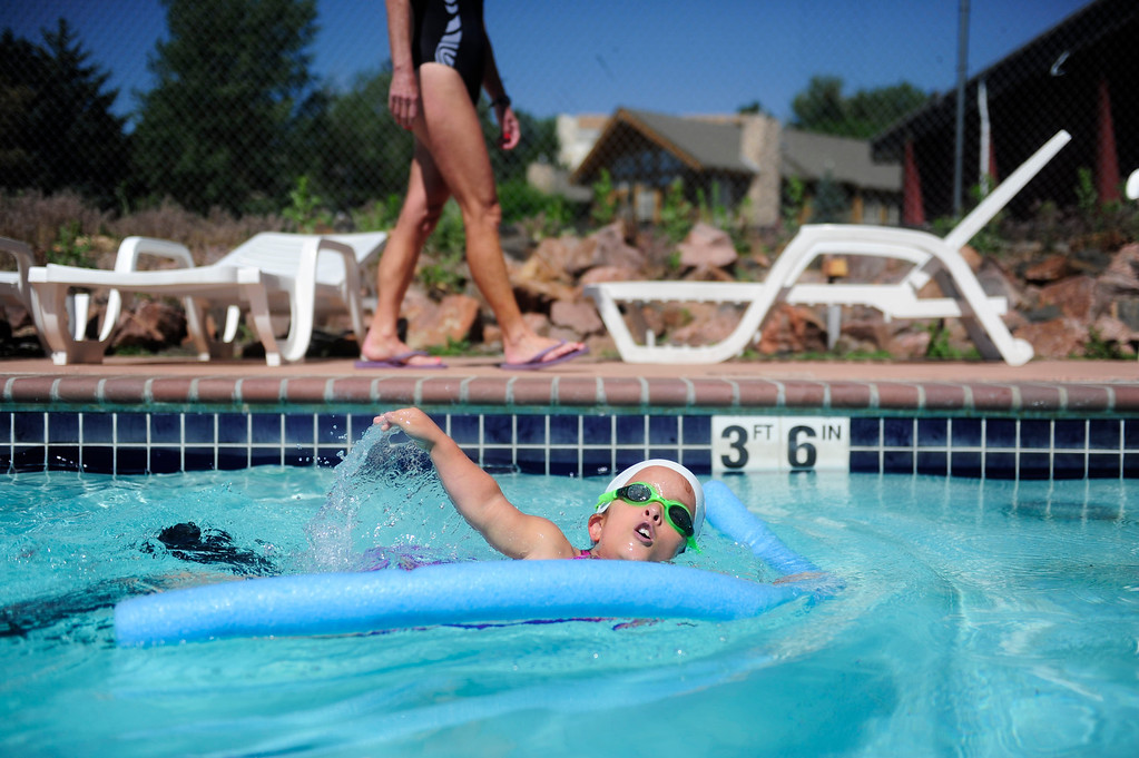 . DENVER - JUNE 19: Mia Towl, 9, warms up with a noodle and flippers during practice with her trainer Laurie Hakala at Point Athletic Club on June 19, 2013. Towl begins training the summer for the 2013 Dwarf Games which take place in August.  (Photo By Grant Hindsley/The Denver Post)