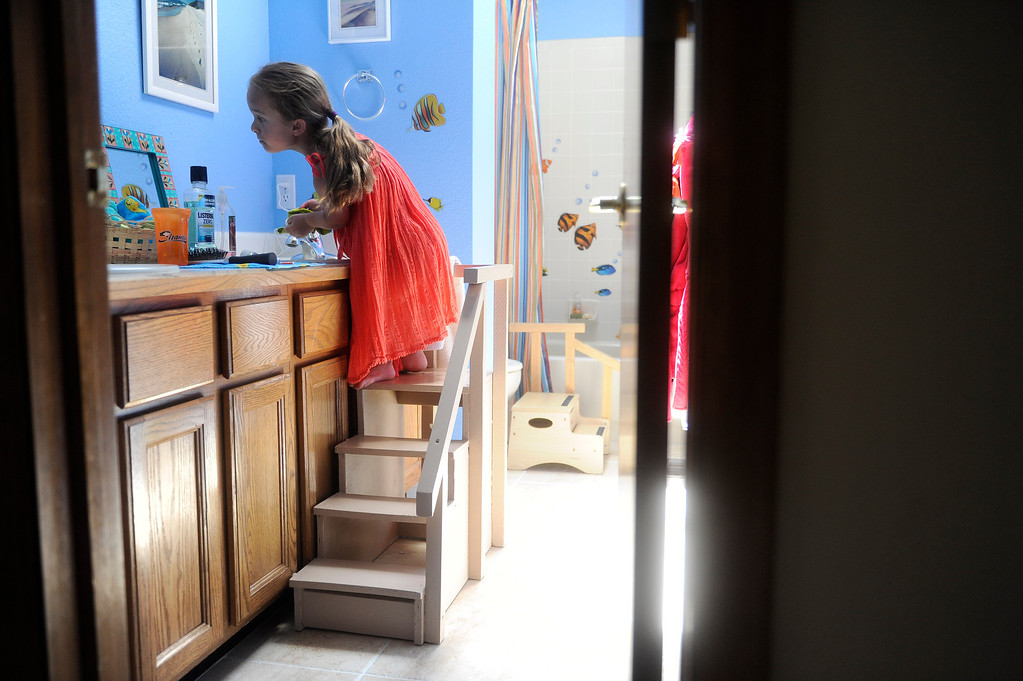 . GOLDEN, CO. - JUNE 22: Mia Towl, 9, washes her face in her bathroom after lunch on June 22, 2013.  (Photo By Grant Hindsley/The Denver Post)