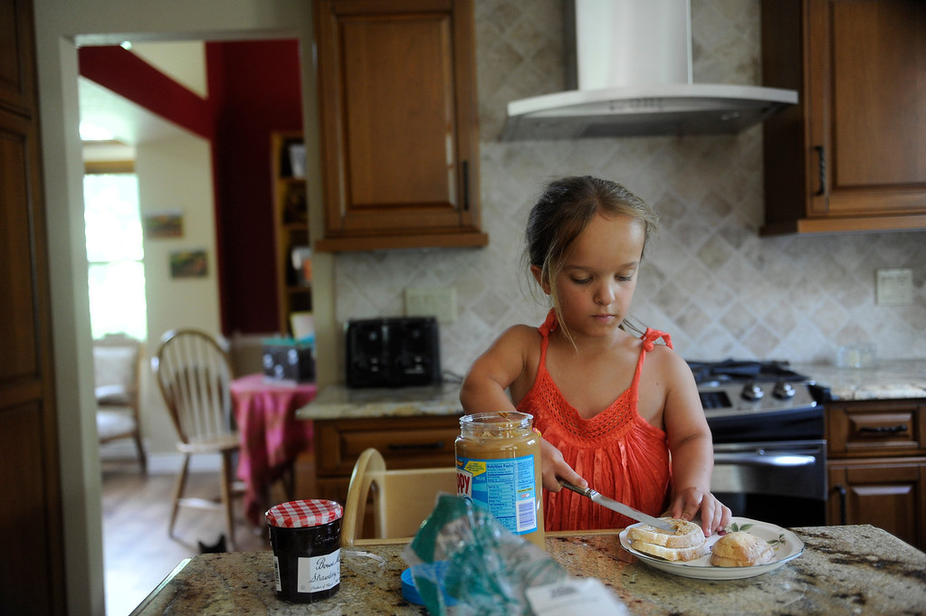 . GOLDEN, CO. - JUNE 22: Mia Towl, 9, makes a peanut butter and jelly sandwich at her home on June 25, 2013. The Towl family has made many adjustments to their home so Mia can have access to all the things she needs. She has a sturdy wooden tower she uses to reach the kitchen counter.  (Photo By Grant Hindsley/The Denver Post)