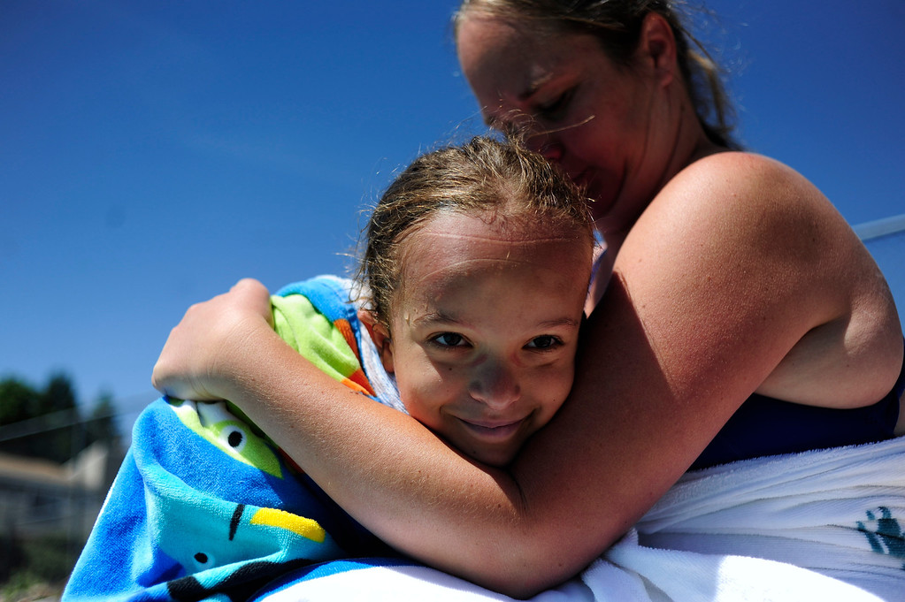 . DENVER - JUNE 19: Mia Towl, 9, smiles while her mother, Lyssa Towl, dries her off after swim practice at Point Athletic Club on June 19, 2013. Towl swims three to four times a week and will soon start training everyday for the 2013 Dwarf Games in Lansing Michigan. (Photo By Grant Hindsley/The Denver Post)