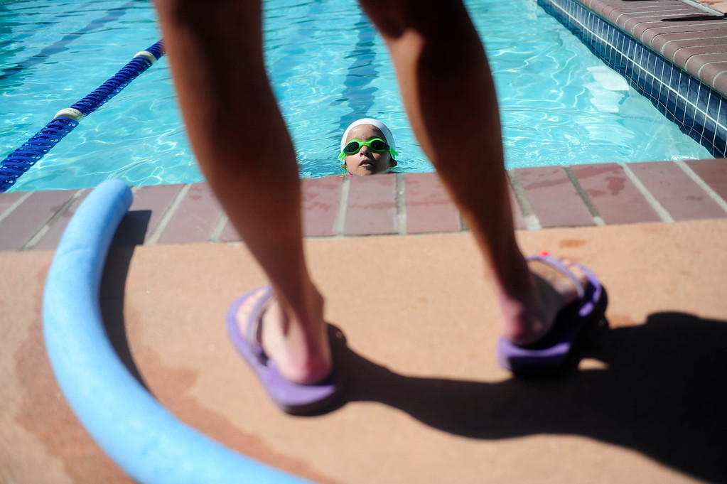 . DENVER - JUNE 19: Mia Towl, 9, peers out of the pool at her trainer Laurie Hakala at the Point Athletic Club on June 19, 2013. Towl begins training the summer for the 2013 Dwarf Games which take place in August.  (Photo By Grant Hindsley/The Denver Post)