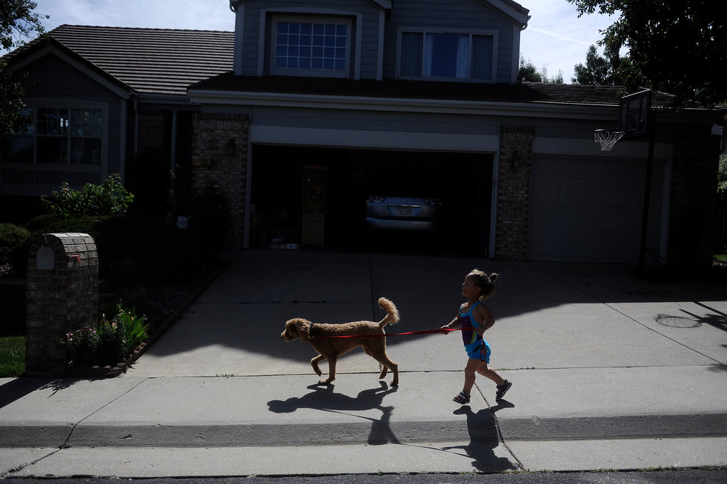 . GOLDEN, CO. - JUNE 25: Mia Towl, 9, takes her dog, Kona, on a run around the neighborhood on June 25, 2013.  (Photo By Grant Hindsley/The Denver Post)