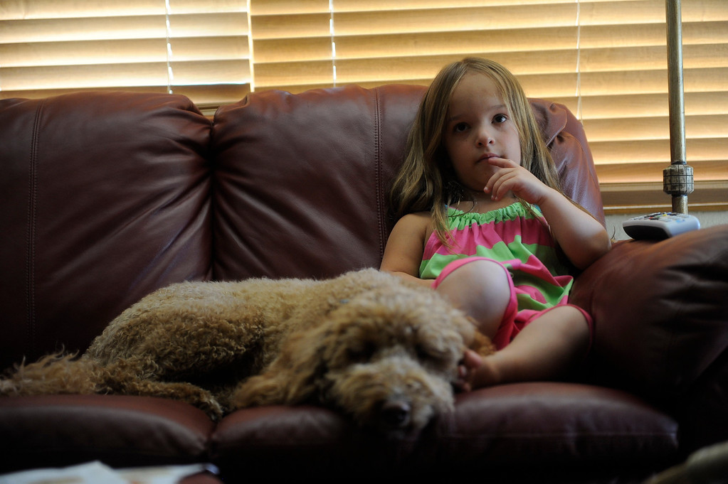. GOLDEN, CO. - JUNE 25: Mia Towl, 9, and her dog, Kona, watch a Peter Rabbit cartoon before heading to summer camp on June 25, 2013.  (Photo By Grant Hindsley/The Denver Post)