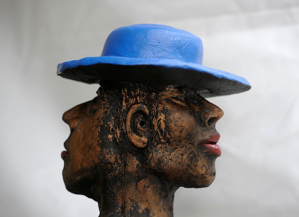 ". DENVER, CO - JULY 27: Lone Tree artist Michaele Greene\'s ""Two Faced\"" clay sculpture peers out to the crowd. The inaugural Cheesman Park Art Fest takes place along the southern edge of the park with about 100 juried artists including works in glass, painters, photographers, jewelers and more from all over the country. The festival will run through Sunday from 10 a.m. to 5 p.m.(Photo By Kathryn Scott Osler/The Denver Post)"