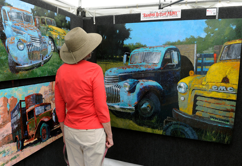. DENVER, CO - JULY 27: A woman pauses in front of the large acrylic paintings by Denver artist Martin Lambuth. Lambuth says he uses a credit card to create his works of art. The inaugural Cheesman Park Art Fest takes place along the southern edge of the park with about 100 juried artists including works in glass, painters, photographers, jewelers and more from all over the country. The festival will run through Sunday from 10 a.m. to 5 p.m. (Photo By Kathryn Scott Osler/The Denver Post)