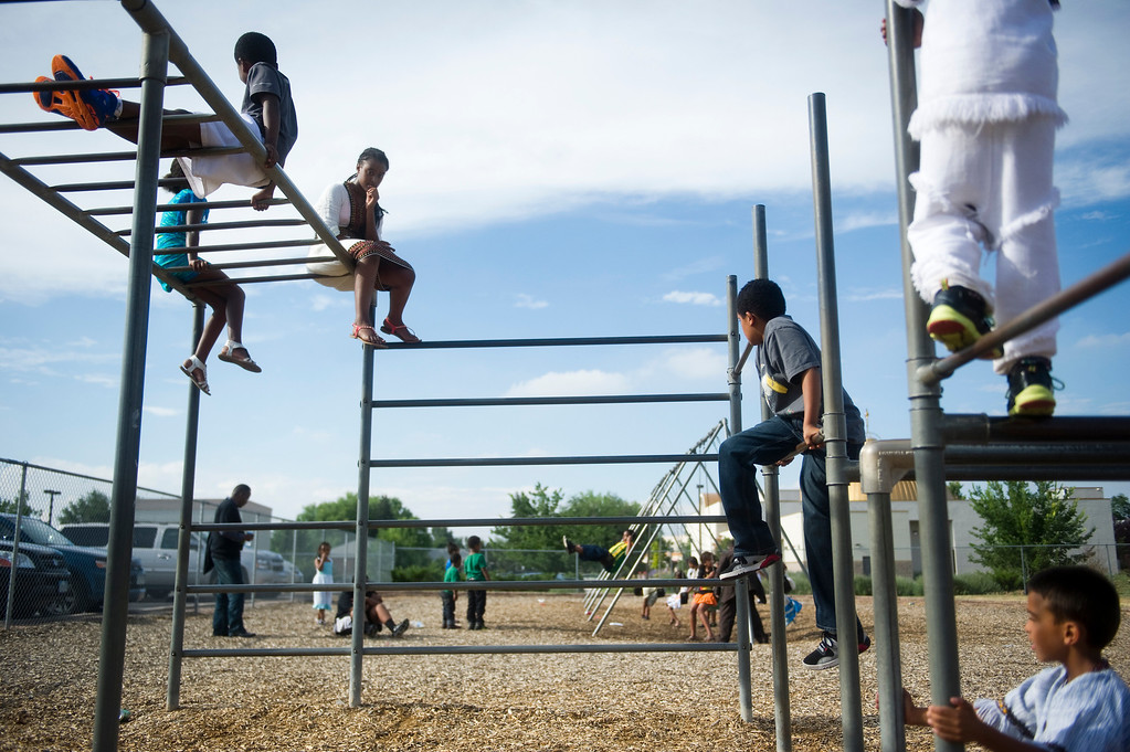. Kids play on a jungle gym outside Taste of Ethiopia Grand Festival at Laredo Elementary School in Aurora, Co, on July 28, 2013. St. Mary\'s Ethiopian Orthodox Church sits behind the school where the festival was held. (Photo By Grant Hindsley/The Denver Post)