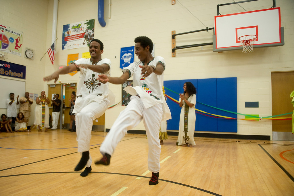 . Nebeu Abraha, left, and David Gelagay perform a traditional dance at the Taste of Ethiopia Grand Festival at Laredo Elementary School in Aurora, Co, on July 28, 2013. (Photo By Grant Hindsley/The Denver Post)