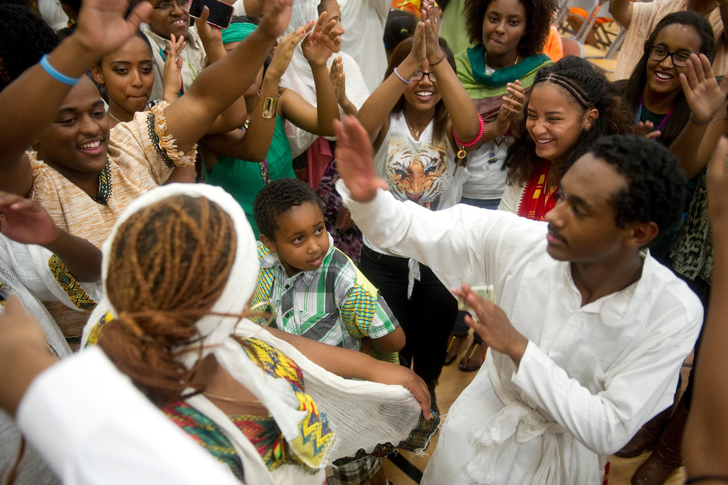 . Yohanis Mekonen, 8, center, looks up while dancing in a circle after the crowd rushed and joined in on the final traditional dance being performed at the Taste of Ethiopia Grand Festival at Laredo Elementary School in Aurora, Co, on July 28, 2013. (Photo By Grant Hindsley/The Denver Post)