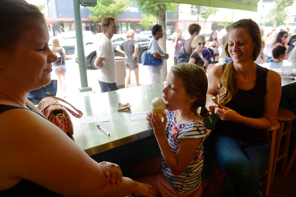. DENVER, CO - AUGUST 03:  Ice cream fan, Payton Anderson, 6, center, enjoys a free ice cream cone at the Sweet Action ice cream shop on Broadway Saturday afternoon August 3, 2013. Payton\'s mother, Julie Anderson, left, and friend, Joanne Bancroft, right await Payton after already enjoying their free cones. Comedy podcasters from Los Angeles California, Jesse Thorn, and Jordan Morris, started a Kickstarter campaign to fund 1000 free ice cream cones to film a documentary.  (Photo By Andy Cross/The Denver Post)