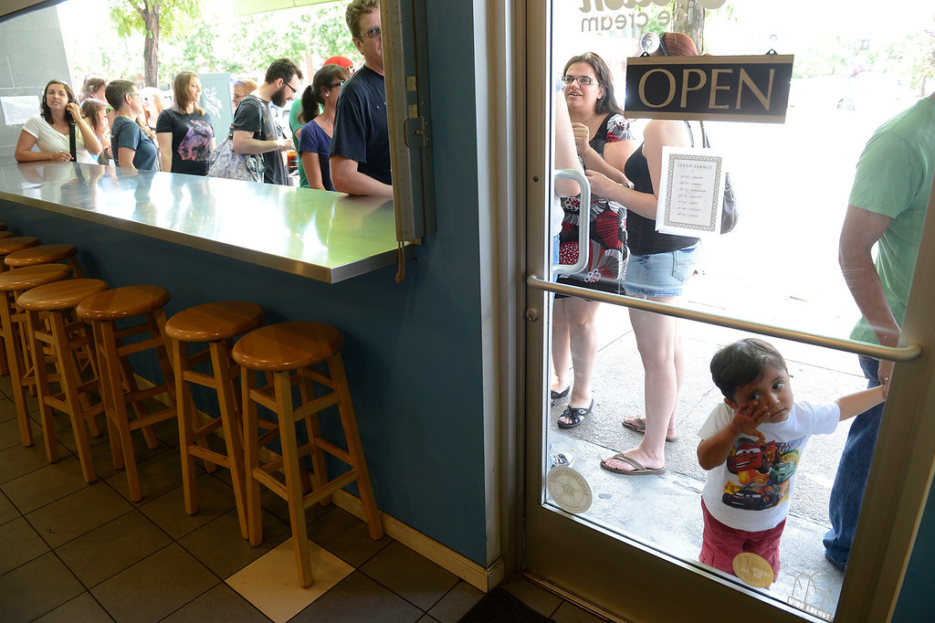 . DENVER, CO - AUGUST 03:  Ice cream fan, Pablo Gutierrez, 2, peers through the front window of the Sweet Action ice cream shop on Broadway in anticipation of free ice cream Saturday afternoon, August 3, 2013. Comedy podcasters from Los Angeles California, Jesse Thorn, and Jordan Morris, started a Kickstarter campaign to fund 1000 free ice cream cones to film a documentary.  (Photo By Andy Cross/The Denver Post)