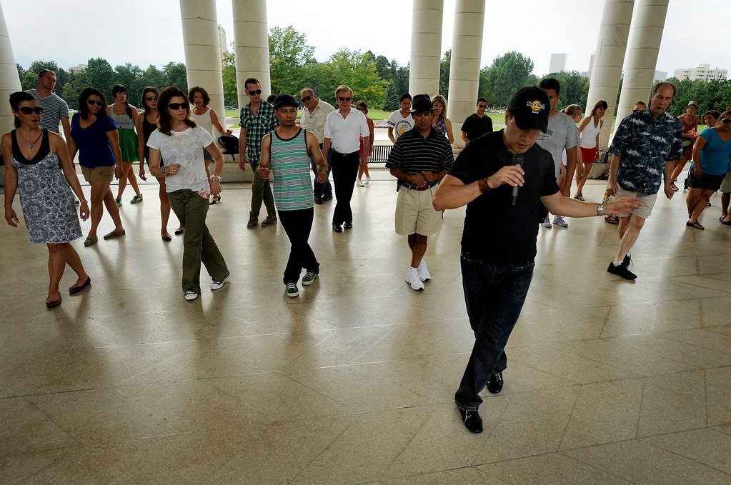 ". Rafael Ayure, right, teaches a group of people basic salsa dance steps during Salsa Central Denver\'s ""Summer Salsa and Bachata Bash\"" on August 18 where people danced zumba, salsa and bachata at Cheesman Park in the Walker Scott Cheesman Pavilion with the help of seasoned instructors. Photo by Jamie Cotten, Special to The Denver Post"