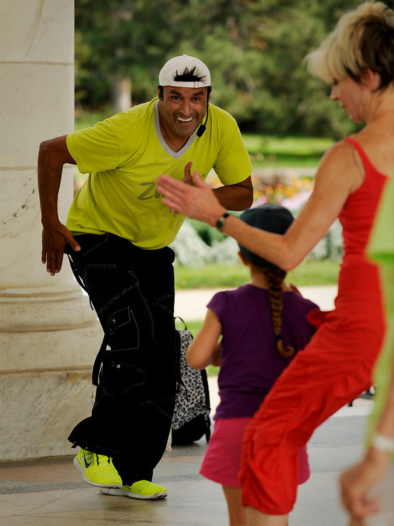 ". Paul Reyes, dance instructor and project manager for a construction company, teaches a large group of people to zumba on August 18 for Salsa Central Denver\'s ""Summer Salsa and Bachata Bash\"" at Cheesman Park in the Walker Scott Cheesman Pavilion. Photo by Jamie Cotten, Special to The Denver Post"