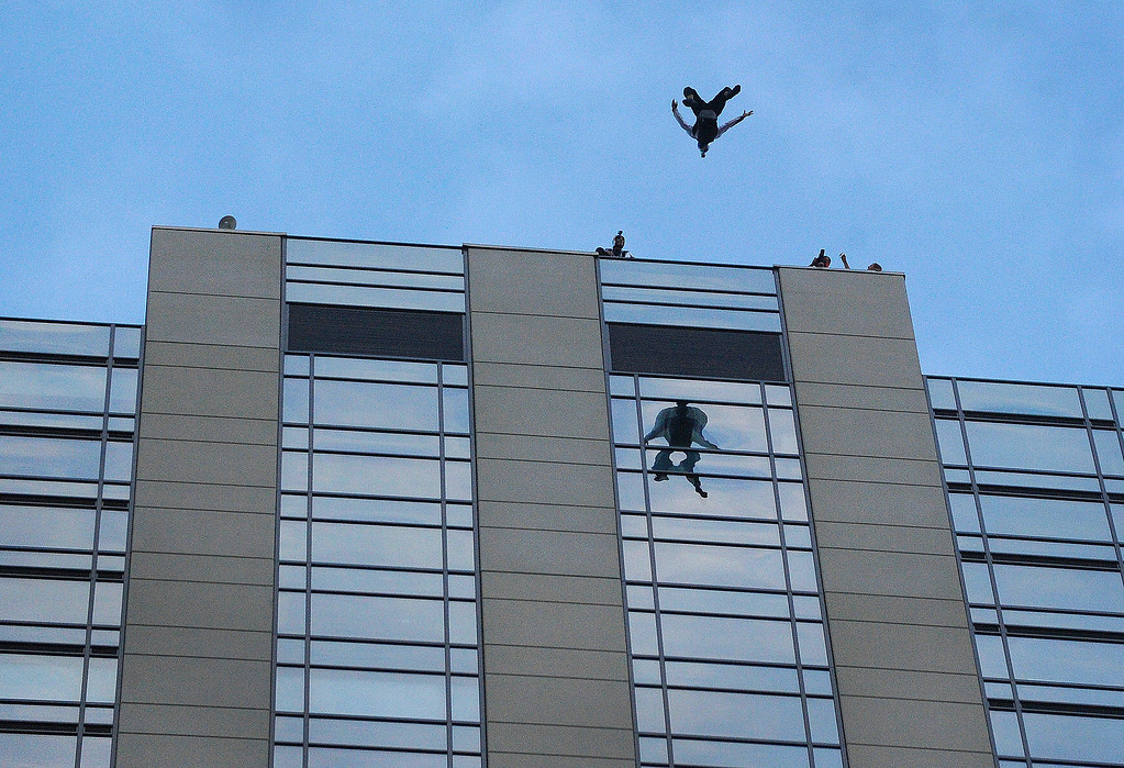 . Miles Daisher did a flip as he jumped from the roof of a downtown Denver hotel Tuesday night.  Photo By Karl Gehring/The Denver Post