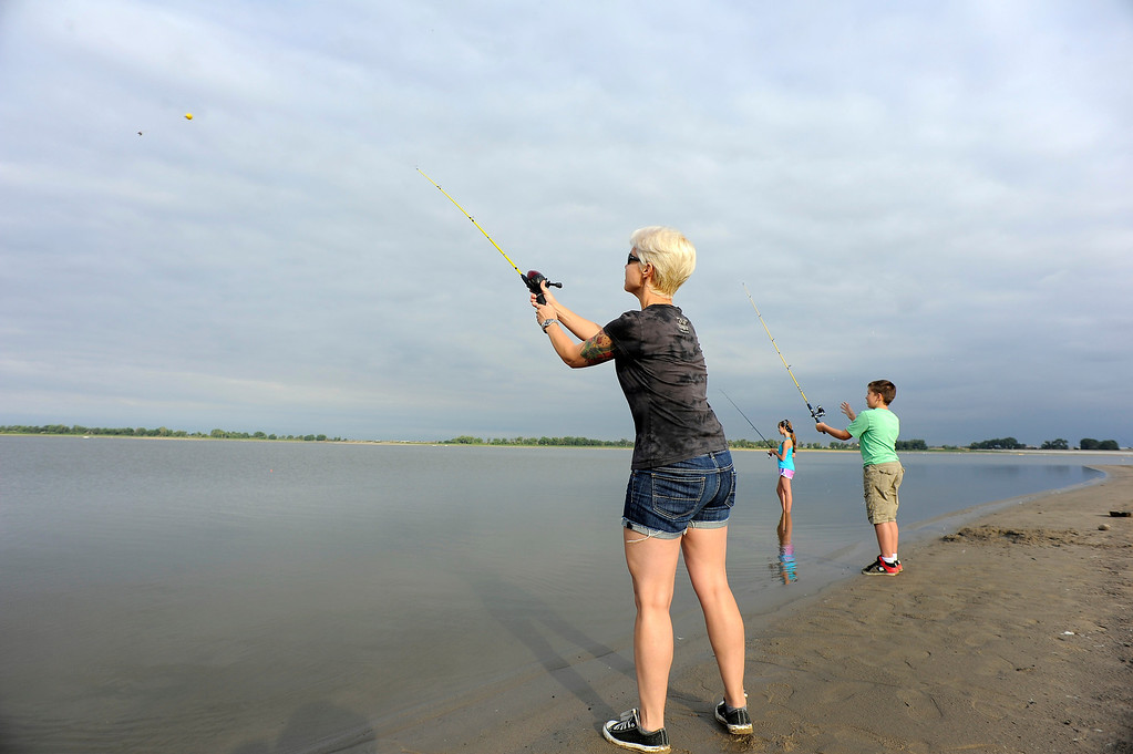 . Christiane Kipphan 43, throws in her line while Adriana Robinson 14, and Julian 12, watch their lines while fishing at Barr Lake September 1, 2013. During the fish salvage anglers can fish without limits with a license. (Photo by John Leyba/The Denver Post)