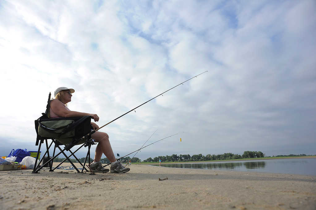 . Cindy Kirker, 55, of Denver sits in her chair as she watches her line while fishing at Barr Lake September 1, 2013. She was hoping to land a catfish during the day. (Photo by John Leyba/The Denver Post)