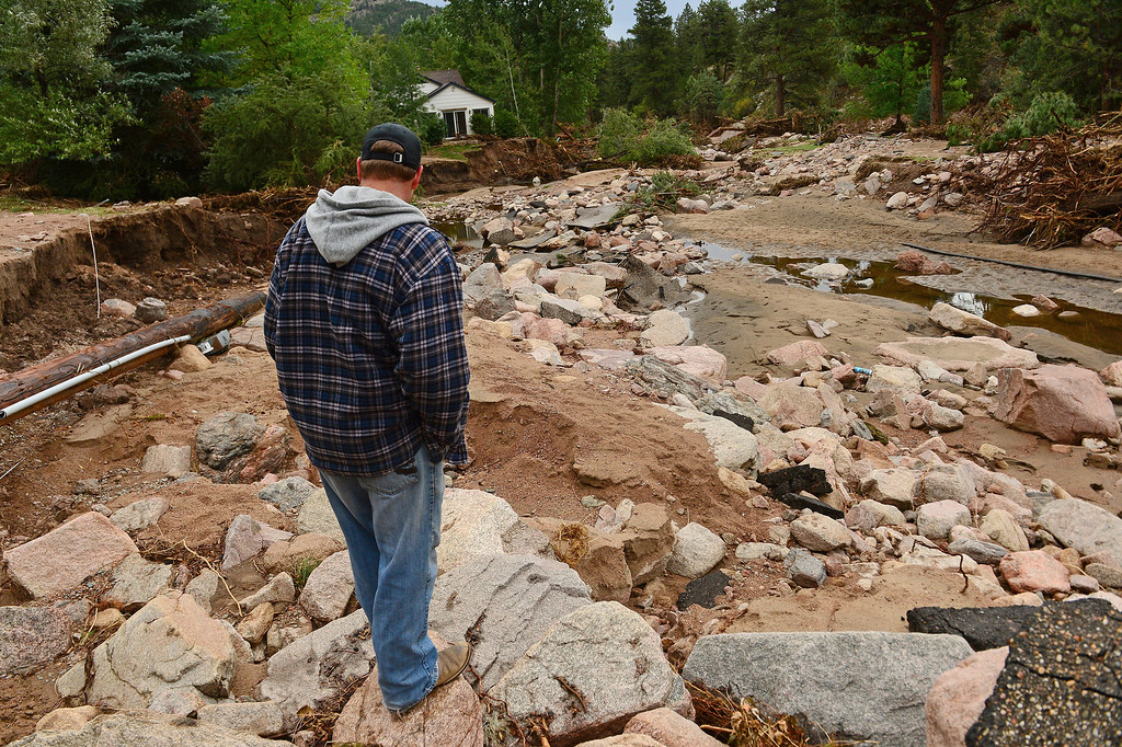 . Pinewood Springs resident Judd Payne looks at the damage to his neighborhood. The flood has rendered their community an island.  He is standing on what used to be Iroquois Road.     (Photo By Helen H. Richardson/ The Denver Post)