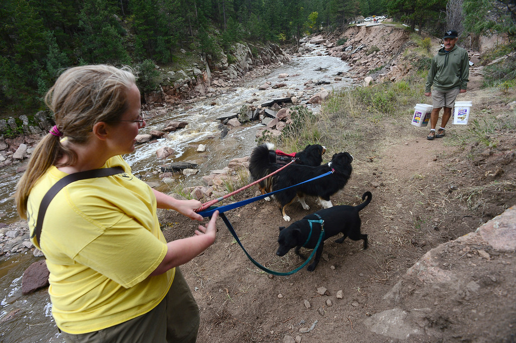 . Pinewood Springs resident Cathy Wise, taking her dogs out for a couple of days, crosses paths with Tom Koby as he heads back with supplies along the newly built trail next to the Little Thompson River, and what used to be Highway 36. She was getting her dogs out for a couple of days to make sure that this access remains open.     (Photo By Helen H. Richardson/ The Denver Post)