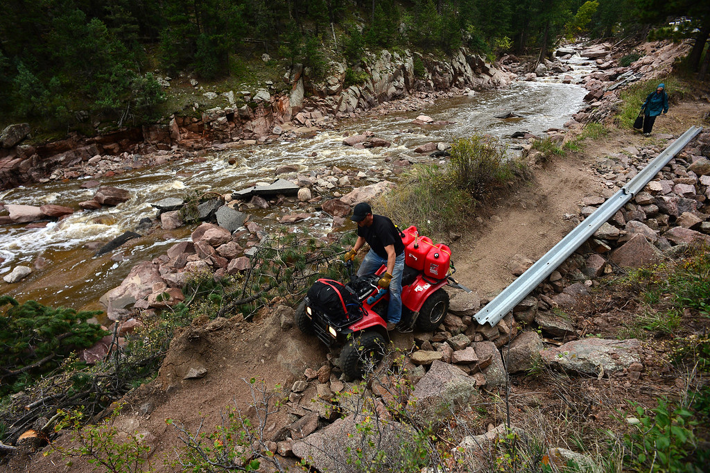 . Pinewood Springs resident Judd Payne brings in supplies on the back of his ATV along the resident\'s new trail next to the Little Thompson River and what used to be Highway 36, west of Pinewood Springs .   (Photo By Helen H. Richardson/ The Denver Post)
