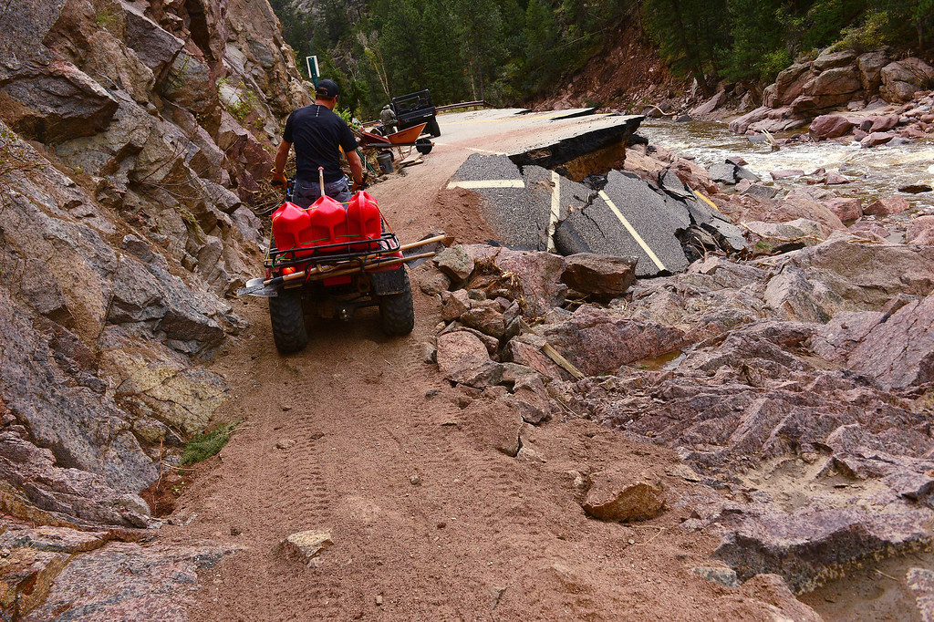 . Pinewood Springs resident Judd Payne brings in supplies on the back of his ATV along the residents\' new trail along the Little Thompson River, and what used to be Highway 36, west of Pinewood Springs, Colorado, on September 22, 2013.  Residents, concerned about their property and never getting help, took things into their own hands. They hand built this trail so they can go west to get to Estes Park. The also built a road that large vehicles could use, which runs to Lyons where they were able to get cars and large vehicles out as well as letting work trucks such as Century Link and Poudre REA in so they could get started on repairing phone and electrical lines. Pinewood Springs is basically an island with all main roads and bridges washed away.    (Photo By Helen H. Richardson/ The Denver Post)