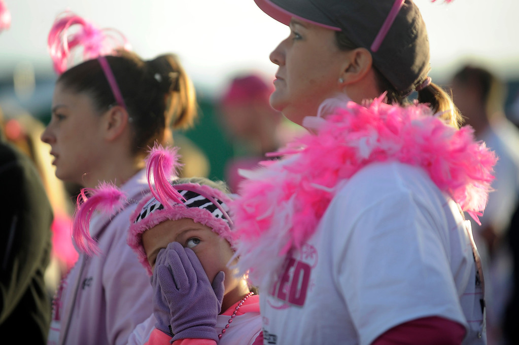 . DENVER, CO - SEPTEMBER 29: Abby Letcher, 8, glances up at her mom, Barb, as she warms her hands by breathing into them during the Susan G Komen Race for the Cure in Denver, Colorado on September 29, 2013. Approximately 30,000 people participated in this years race. (Photo by Seth McConnell/The Denver Post)