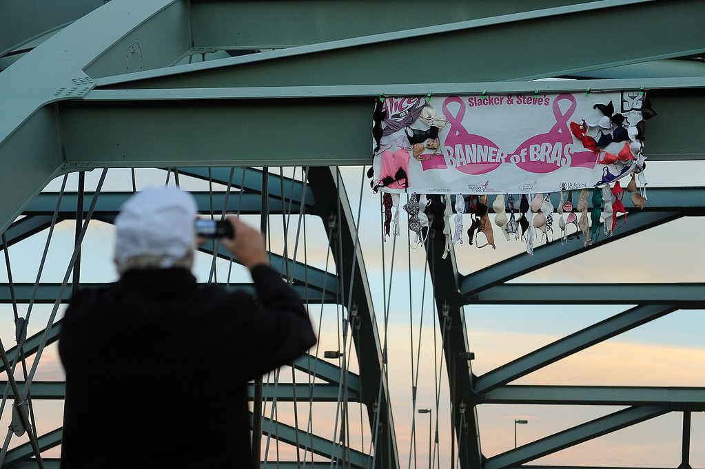 . DENVER, CO - SEPTEMBER 29: A racer stops to take a photo of a banner during the Susan G Komen Race for the Cure in Denver, Colorado on September 29, 2013. Approximately 30,000 people participated in this years race. (Photo by Seth McConnell/The Denver Post)