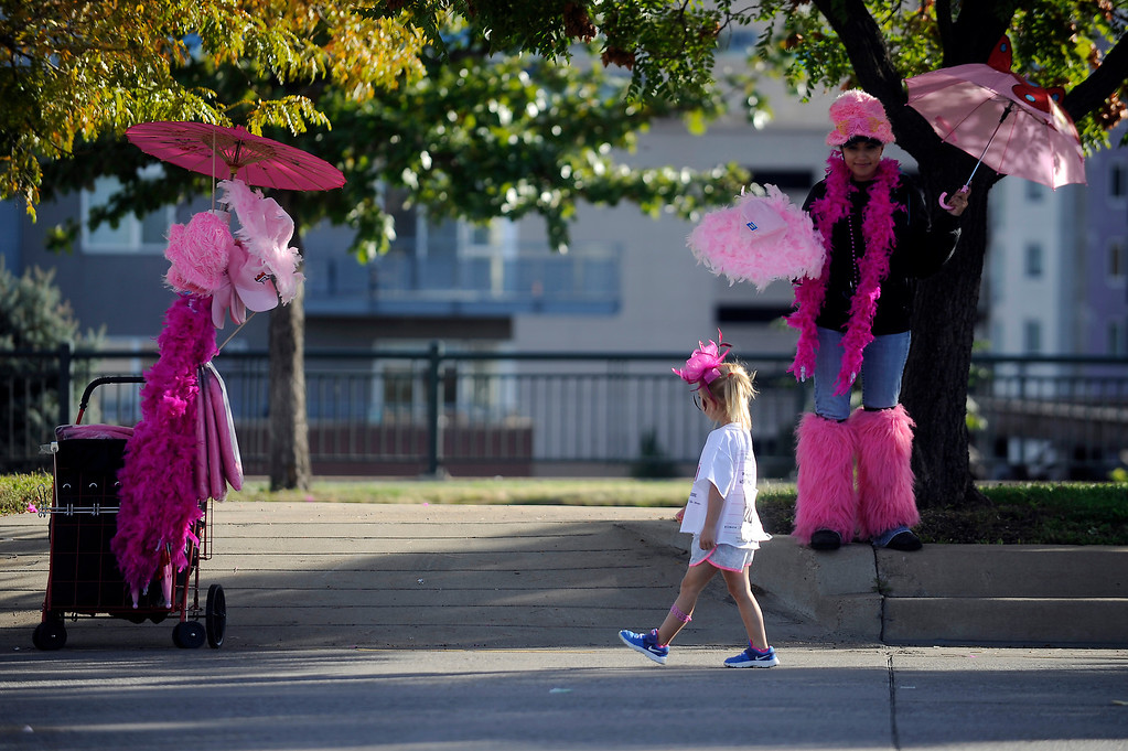 . DENVER, CO - SEPTEMBER 29: Jordan Stransky watches as a young girl approaches her cart full of pink items during the Susan G Komen Race for the Cure in Denver, Colorado on September 29, 2013. Approximately 30,000 people participated in this years race. (Photo by Seth McConnell/The Denver Post)