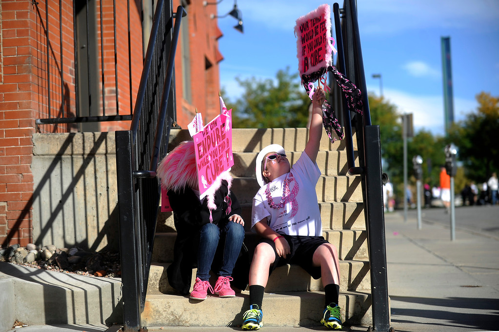 . DENVER, CO - SEPTEMBER 29: Carson Fulton, 11, raises his home made sign high as Madison Smith, 11, uses her to block the sun as the two wait to participate in the family run during the Susan G Komen Race for the Cure in Denver, Colorado on September 29, 2013. Approximately 30,000 people participated in this years race. (Photo by Seth McConnell/The Denver Post)