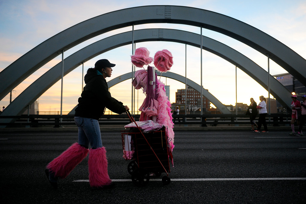 . DENVER, CO - SEPTEMBER 29: Jordan Stransky pushes a cart full of pink merchandise down Speer Blvd during the Susan G Komen Race for the Cure in Denver, Colorado on September 29, 2013. Approximately 30,000 people participated in this years race. (Photo by Seth McConnell/The Denver Post)