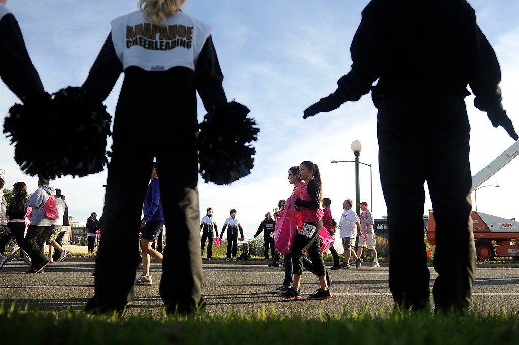 . DENVER, CO - SEPTEMBER 29: The Arapahoe High School cheerleaders cheer on race participants during the Susan G Komen Race for the Cure in Denver, Colorado on September 29, 2013. Approximately 30,000 people participated in this years race. (Photo by Seth McConnell/The Denver Post)