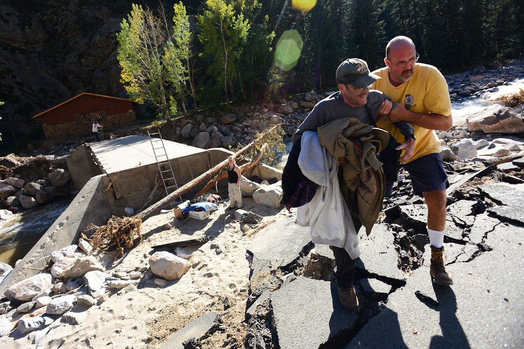 . DRAKE, CO - OCTOBER 1:  Drake resident John Claus helps cabin caretaker Doug Smith, with some of his personal effects, up a steep incline onto Highway 34 in Drake, Co. October 1, 2013.  Claus, Smith and their neighbors were allowed into their homes for the first time since the floods almost three weeks ago.  Many of the homes are still standing but the surrounding property, the bridge and the highway are destroyed.  (Photo By Helen H. Richardson/ The Denver Post)