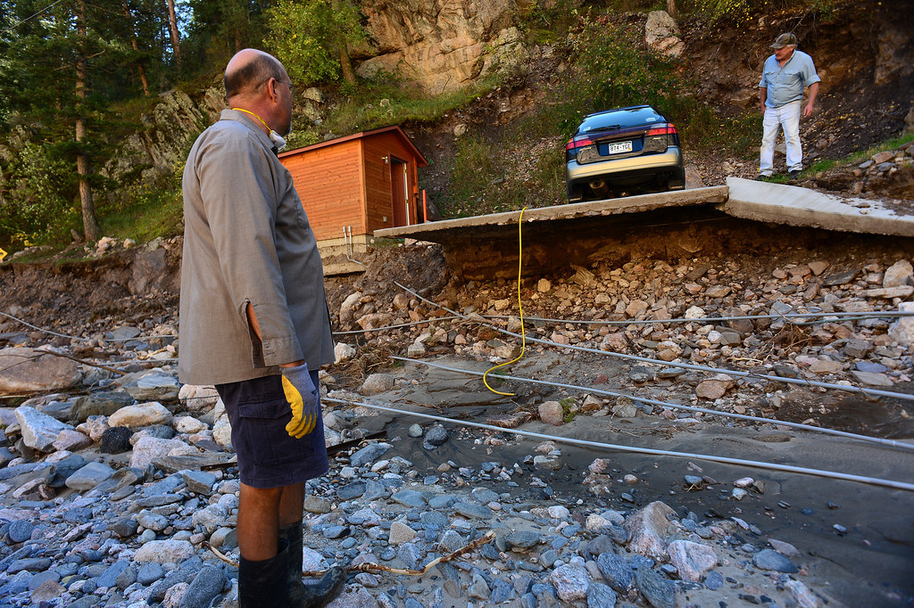 . DRAKE, CO - OCTOBER 1:  John Claus, left, talks with neighbor Richard McGurn, as they look at the damage around their homes  in Drake, Co. October 1, 2013.  The river came so high that it deposited all of the rocks and took away the road that led into their homes. Residents of the town of  Drake were allowed back into their homes for a limited amount of time to see if their homes were still there and to gather personal effects.   Many of the homes are still standing but the surrounding property, the bridges and the many portions of the highway are destroyed.  (Photo By Helen H. Richardson/ The Denver Post)