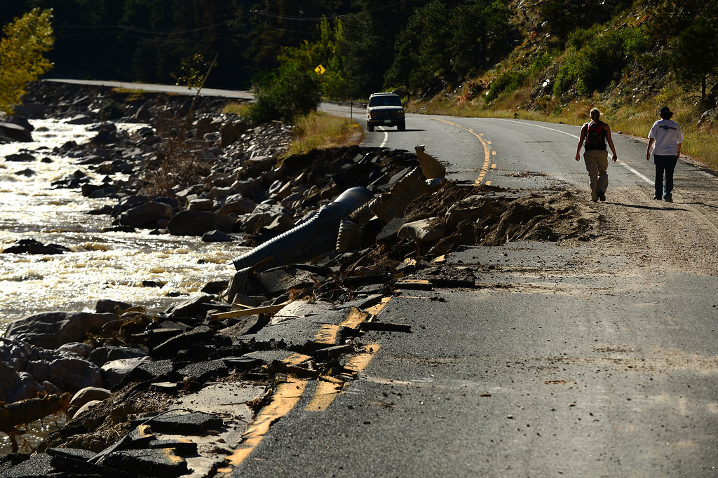 . DRAKE, CO - OCTOBER 1:  Drake resident Heather McGurn, right and her friend Amber Okuley, middle, walk past a destroyed section of Highway 34 near Drake, Co on October 1, 2013.  Some residents were allowed back into their homes for a limited amount of time to see if their homes were still there and to gather personal effects.   Many of the homes are still standing but the surrounding property, the bridges and the many portions of the highway are destroyed.  (Photo By Helen H. Richardson/ The Denver Post)